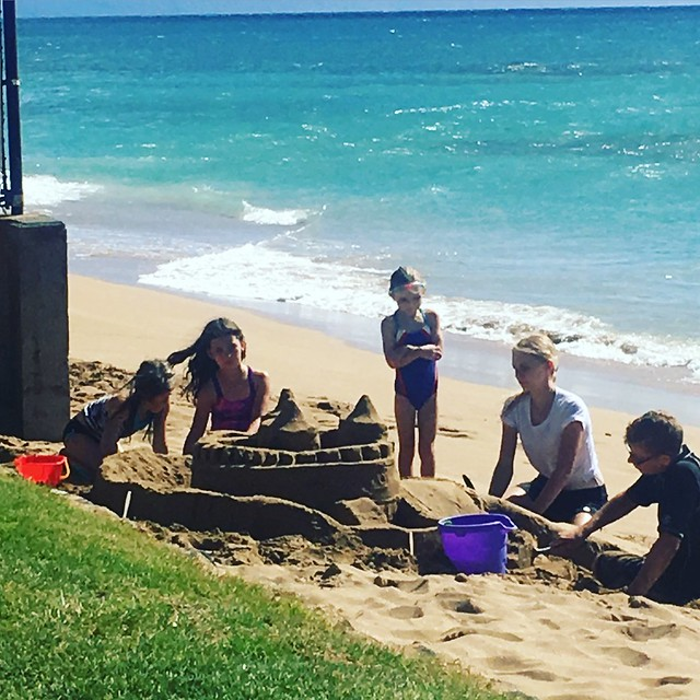 the girls help build a sandcastle
