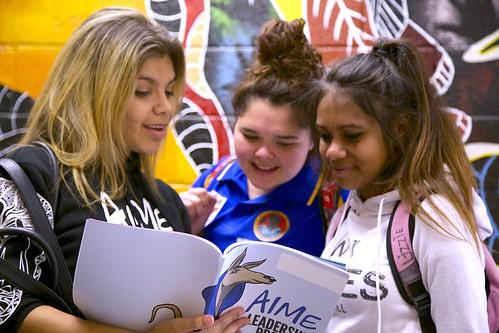 Group of female mentees looking at workbook