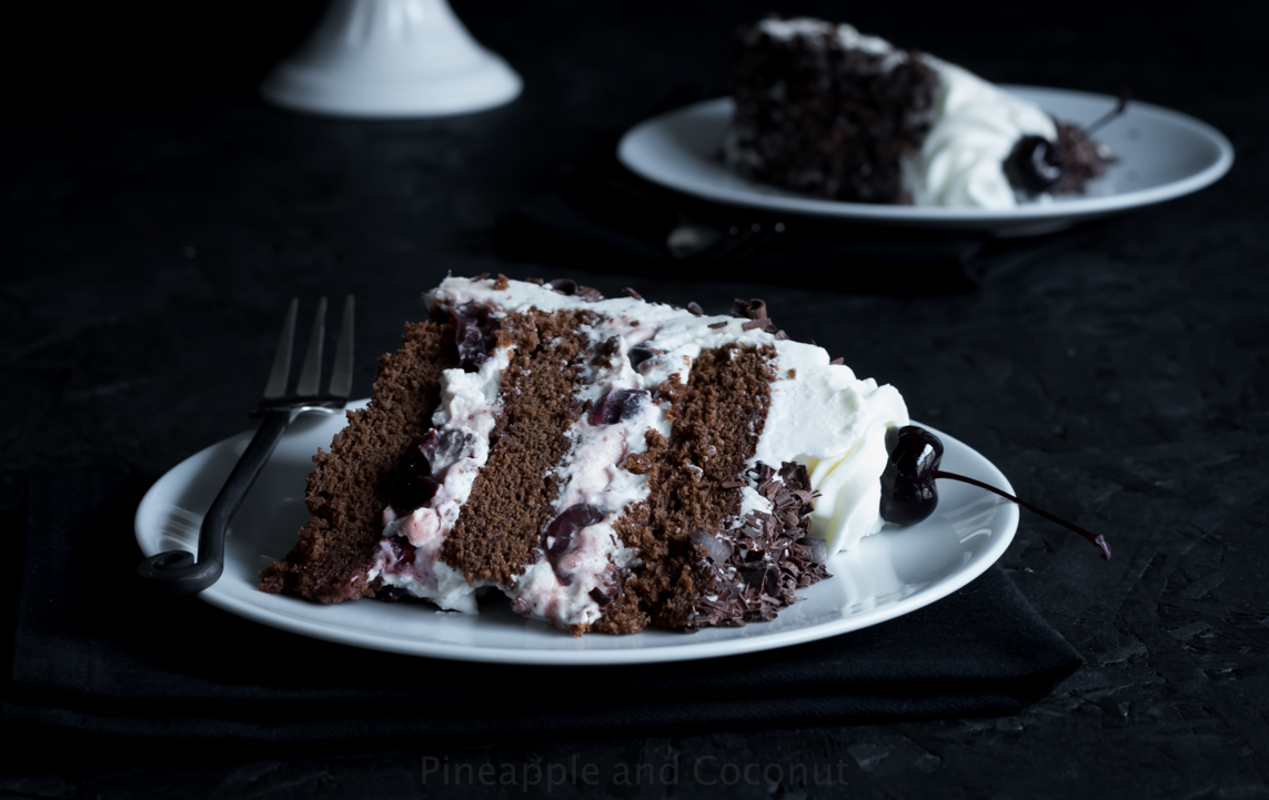 slice of chocolate layer cake on white plate, cake filled with whipped cream and cherries, chocolate curls, fork