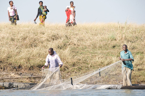Women head to market, as men pull in nets, Zambia. Photo By Patrick Dugan