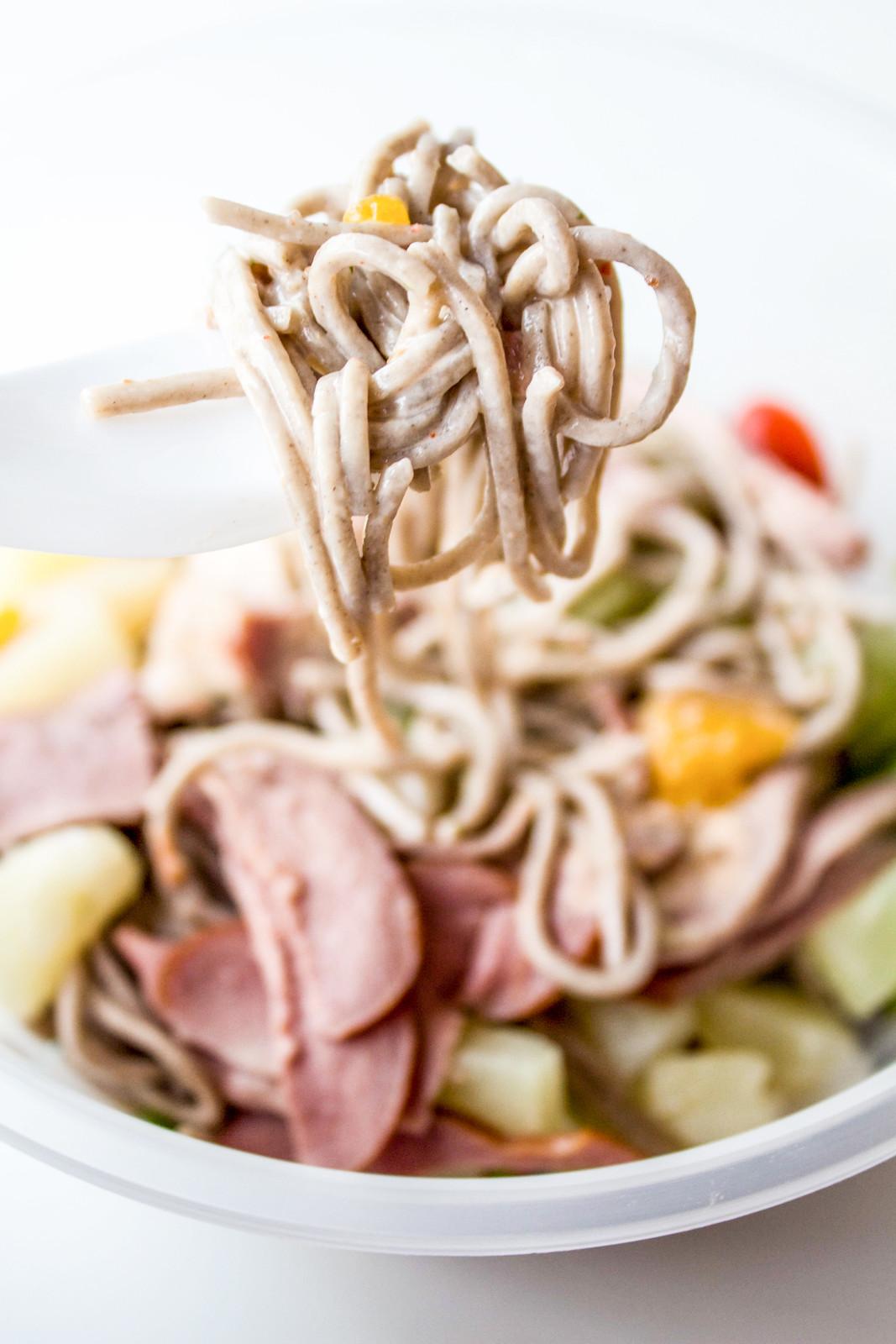 花式小贩食品:白桌子上的蔬菜沙拉和叉子上的酱汁