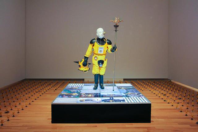 《アトムスーツ・プロジェクト:大地のアンテナ》 自身が、空也上人立像(六波羅蜜寺)を模したポーズで、ヘルメットを脱いで、口から6体のフィギュアを出している彫像。台座は、チェルノブイリの地図とポジフィルムやプリントされた記録写真がバックライトで照らさている。周囲にある無数のフィギュアは、放射線を検知すると光るものが含まれている。予知できない不可視の自然放射線を検知するセンサーと、不可視なものを感知して表現するアーティストである自分とを重ね合わせ、閉じられた妄想から開かれた現実へと移行していく予兆に満ちた作品。