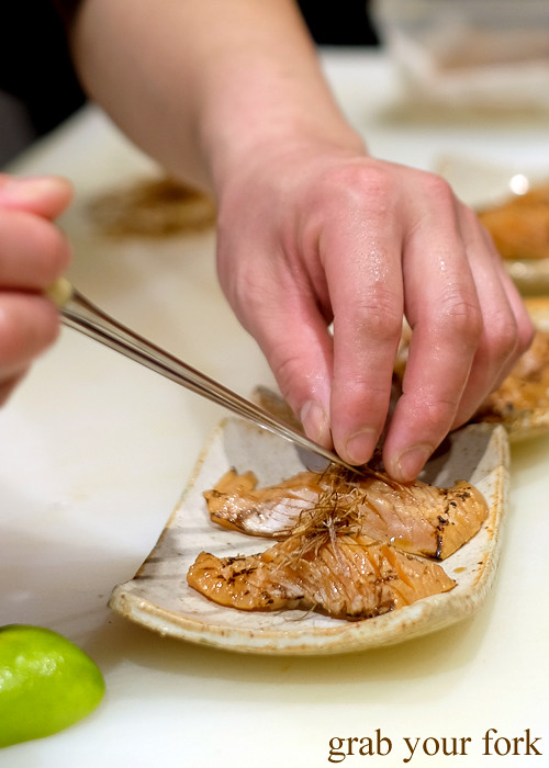 Sushi chef Tomoyuki Matsuya adding crispy leeks to seared salmon nigiri sushi at Hana Ju-Rin in Crows Nest Sydney