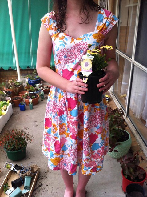 A woman wearing the Sewaholic Cambie dress in a vintage floral print. She is holding a pot of flowers.