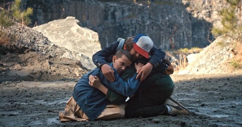 Eleven Mike e Dustin se abraçam em cima de um rochedo perto de um penhasco