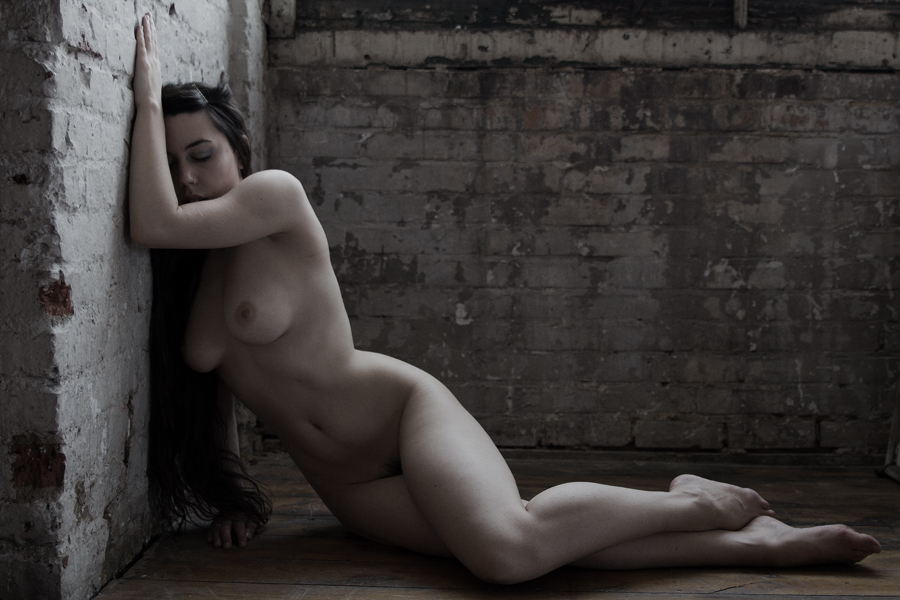 Soft, artistic nude image of a woman in an old building