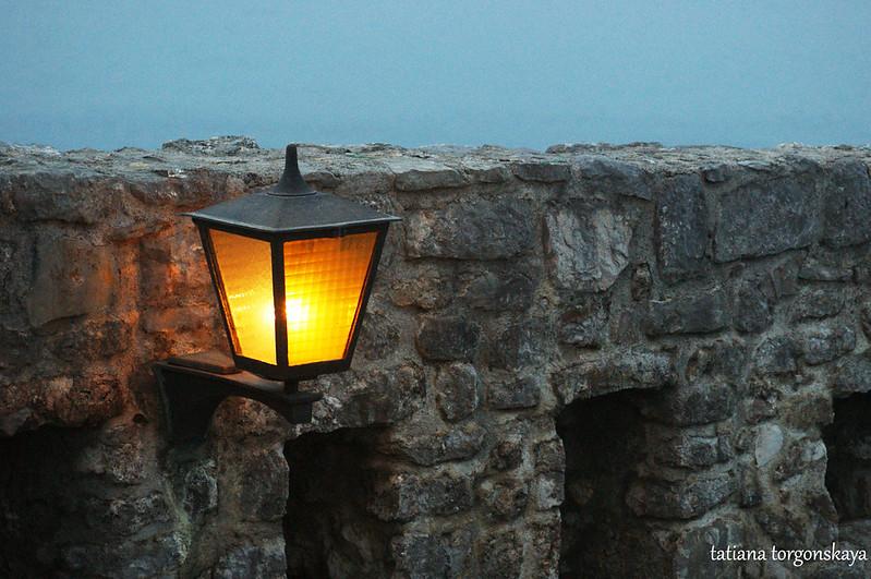 Горящий фонарь на крепостной стене