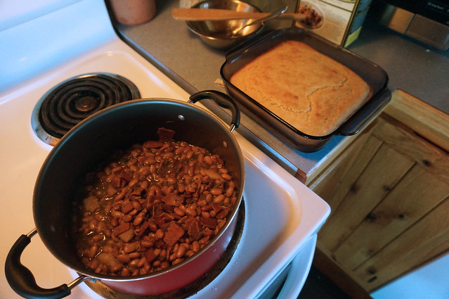 A pot of beans sits on the stove, nubbins of bacon poking out around the legumes. On the counter nearby, a square pan of cornbread is ready for its bean-bath.