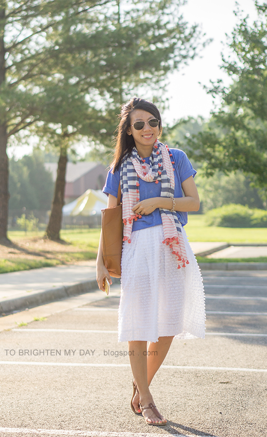 striped and pom pom scarf, cornflower blue tee, pave link bracelet, white clip dot midi skirt, cognac brown tote, brown sandals